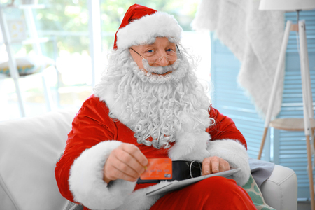 Santa Claus with credit card and tablet on couch at home Standard-Bild