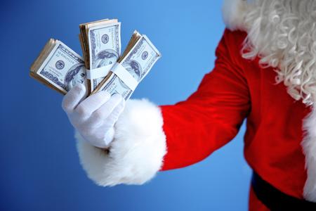 Santa Claus hand holding money on blue background Standard-Bild