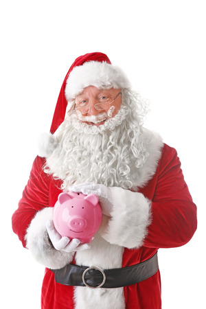 Santa Claus holding piggy bank on white background Standard-Bild