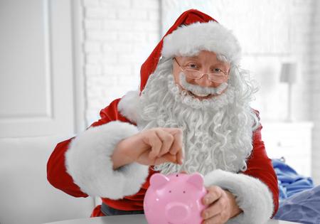 Santa Claus putting coin into piggy bank at home Standard-Bild