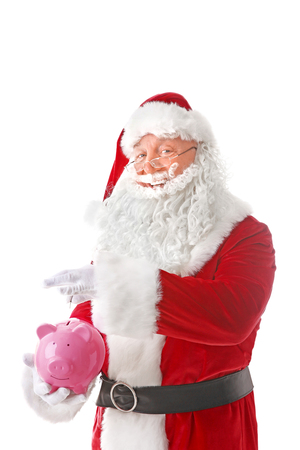 Santa Claus putting coin into piggy bank on white background