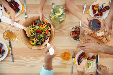People having barbecue picnic at wooden table, top view