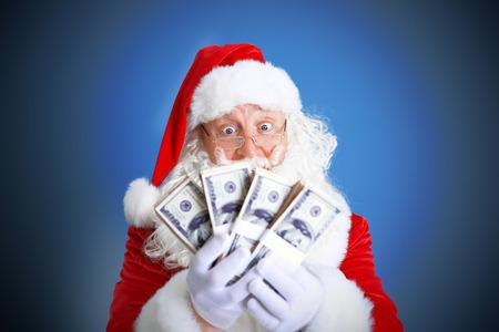 Santa Claus holding money on blue background
