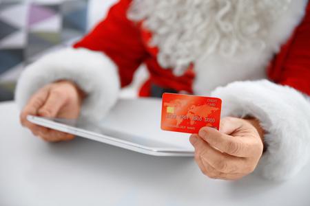Santa Claus with credit card and tablet at home, closeup