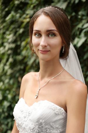 Beautiful bride on blurred green foliage background