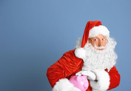 Santa Claus holding piggy bank on blue background Standard-Bild