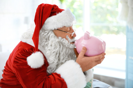 Santa Claus with piggy bank at home