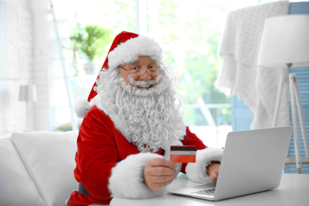 Santa Claus with credit card and laptop at home Standard-Bild