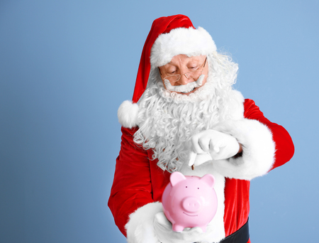 Santa Claus putting coin into piggy bank on blue background