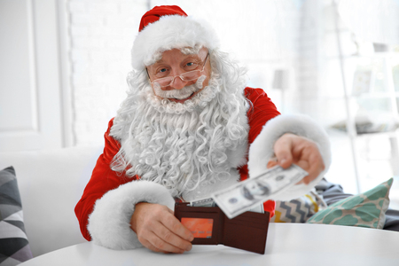 Santa Claus holding wallet with money and credit card at home