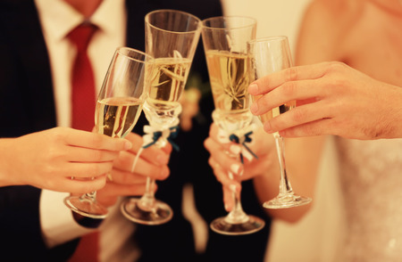 Hands with champagne glasses on wedding dinner