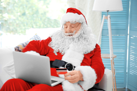 Santa Claus with credit card and laptop on couch at home
