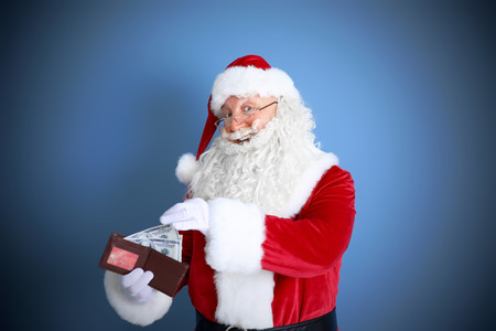 Santa Claus holding wallet with money and credit card on blue background