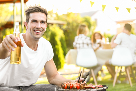 Young man with bottle of beer preparing barbecue Standard-Bild