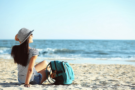 Tourist girl with backpack on beach Stock Photo