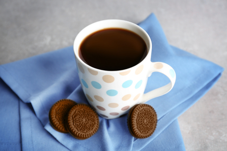 Cup of coffee and chocolate cookies with cream on napkin