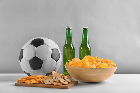 Beer with snacks and football ball on light background