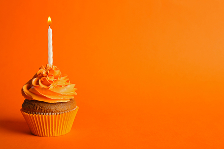 Fresh tasty cupcake with candle on orange background
