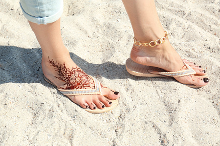 Female legs with henna tattoo on beach sand background
