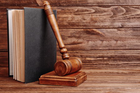 Judge's gavel and book on wooden wall background
