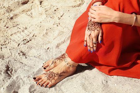 Female legs and hands with henna tattoo on beach sand background Banque d'images