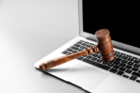 Wooden judge's gavel on laptop keyboard, closeup Banco de Imagens