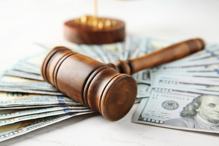 Judge's gavel and dollar banknotes on white table