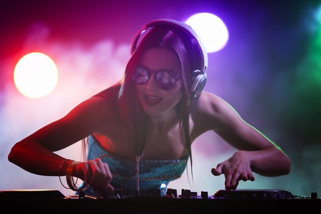 Pretty young DJ playing music in nightclub