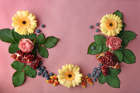 Composition of flowers, pomegranate pieces and berries on pink background Banque d'images