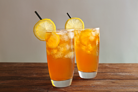 Glass of iced tea with lemon slices on wooden table Stock Photo