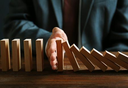 Mano di uomo d'affari che cerca di smettere di far cadere il Domino sul tavolo Archivio Fotografico