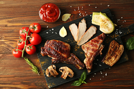 Grilled meat with vegetables on cutting board on wooden background