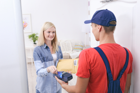 Young woman paying for package from courier Stock Photo