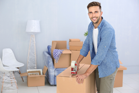House moving concept. Man packing cardboard box