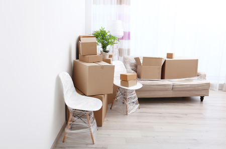 House moving concept. Boxes and furniture in new living room