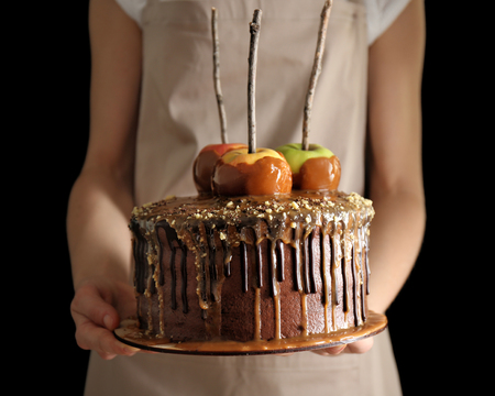 Woman holding chocolate cake with apples on black background 写真素材