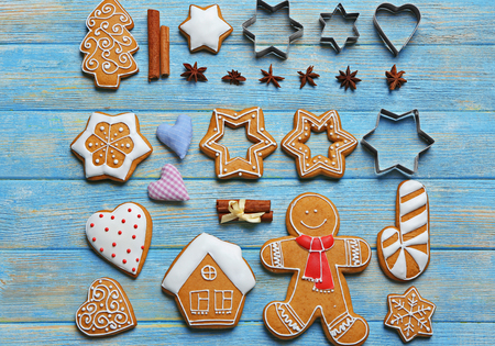 Delicious Christmas cookies with cutters on wooden background