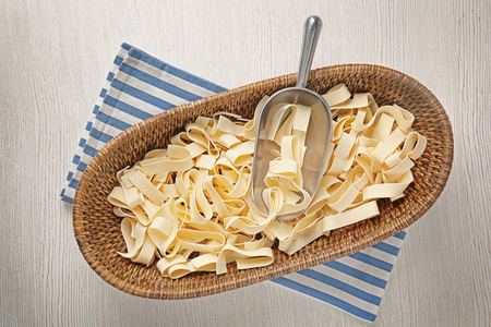 Metallic scoop with pasta on wooden background Stock Photo