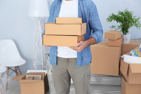 House moving concept. Man holding cardboard boxes, closeup Stock Photo