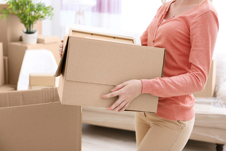House moving concept. Woman holding cardboard box, closeup