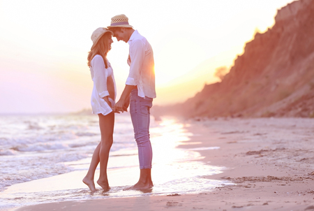 Young happy couple on beach on cliff background 스톡 콘텐츠