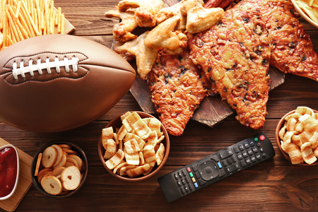 Tasty snacks, remote control and rugby ball on wooden table Stock Photo