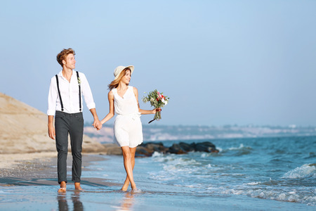 Young happy couple walking on seashore Banco de Imagens