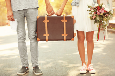 Just married couple holding vintage suitcase and walking in park