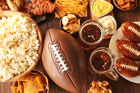 Table full of tasty snacks and beer prepared for watching rugby on TV Фото со стока