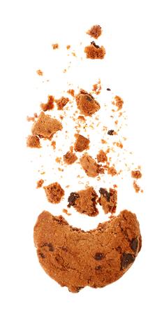 Leckerer Keks mit Schokoladenstückchen und Krümeln auf weißem Hintergrund