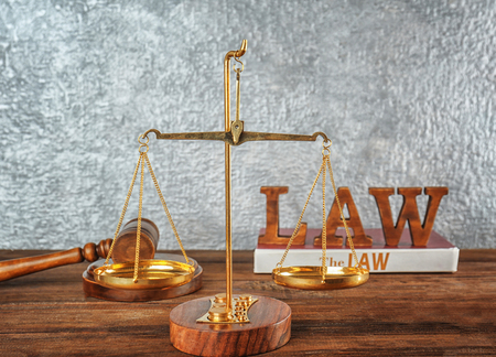 Scales of justice on wooden table, closeup