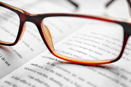 Glasses on open book, close up view. Healthy eyes concept Stock Photo