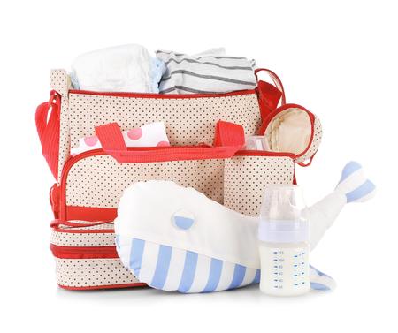 Bolsa de madres con juguetes y accesorios sobre fondo blanco. Foto de archivo