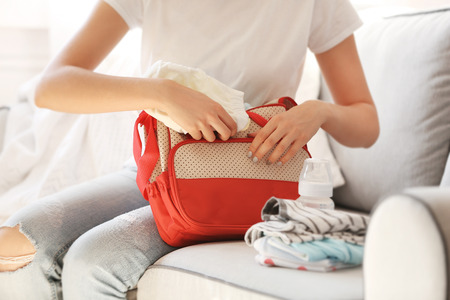Woman packing her bag with child stuff on couch Standard-Bild